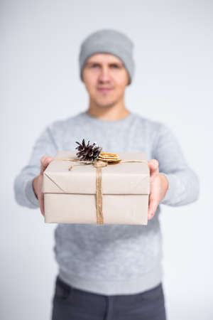 christmas gift box in male hands over gray background Фото со стока