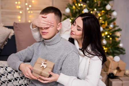 christmas, new year, love and surprise concept - beautiful woman surprising her boyfriend with Christmas gift at home near Christmas tree