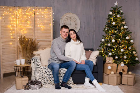 christmas and love concept - young beautiful couple sitting in living room with Christmas tree Фото со стока - 133346770