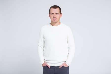 portrait of young man in warm winter sweater posing over gray background with copy space