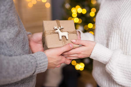 christmas, new year and love concept - close up of man giving gift box to his girlfriend in decorated room with garland and Christmas tree