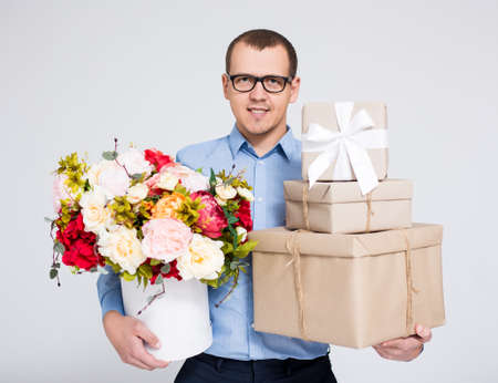 valentines day or mothers day concept - portrait of young handsome man holding flowers and heap of gift boxes over gray background Фото со стока