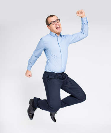 success concept - portrait of cheerful young handsome businessman celebrating something and jumping over gray background
