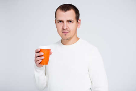 portrait of young man in warm winter sweater drinking coffee or tea over gray background with copy space Фото со стока