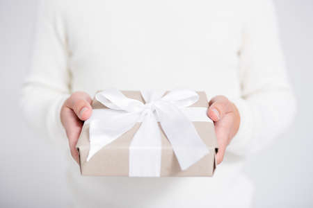 Christmas or Valentines day concept - gift box in male hands over gray background