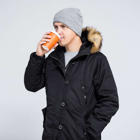 young handsome man in warm winter jacket drinking coffee or tea over gray background