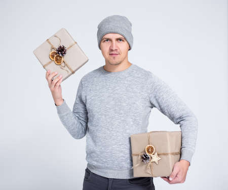 winter and holidays concept - portrait of cheerful young man in warm winter clothes posing with gift boxes over gray background Фото со стока