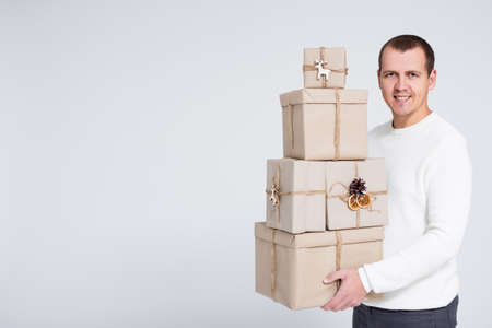 Christmas or Valentines day background - young handsome man in white warm sweater holding gift boxes over gray background with copy space