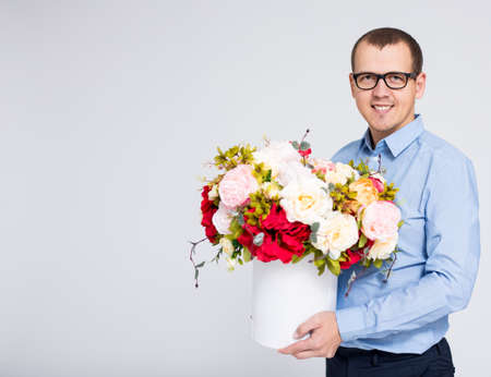 valentines day or mothers day concept - portrait of young handsome man with flowers box over gray background with copy space
