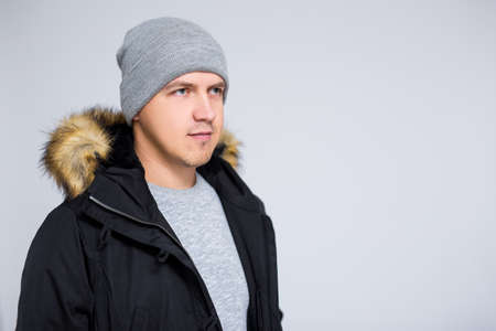 portrait of young man in warm winter clothes posing over gray background Фото со стока