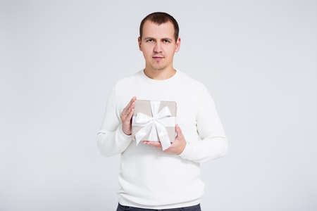 portrait of young man in warm winter sweater holding gift box over gray background with copy space