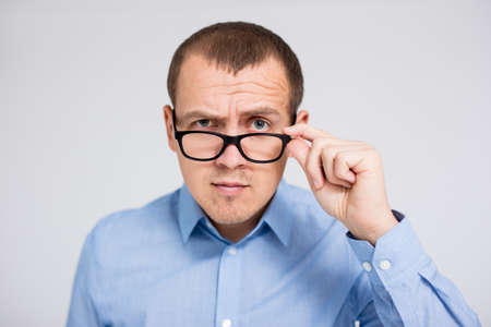portrait of young serious businessman in eyeglasses looking at camera over gray background Фото со стока