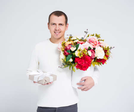 Valentines day concept - handsome man holding bouquet of flowers and gift box over gray background
