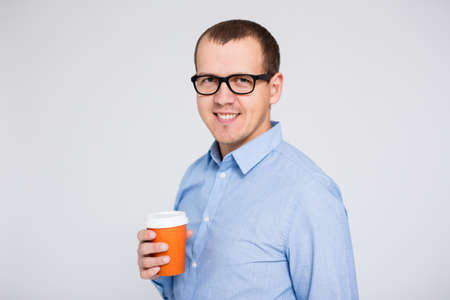 portrait of young businessman in eyeglasses with cup of coffee or tea over gray background