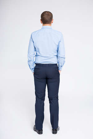 back view of full length businessman over gray background Фото со стока