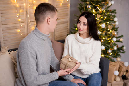 christmas and love concept - handsome man giving Christmas present to his girlfriend
