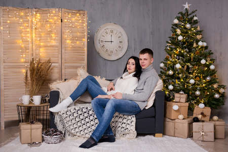concept - portrait of young beautiful couple in love sitting near decorated Christmas tree at home
