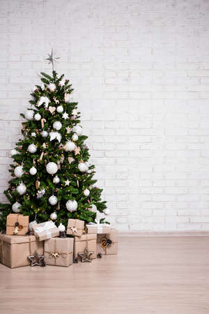 christmas and new year background - decorated christmas tree and gift boxes over white brick wall with copy space Фото со стока - 133386495