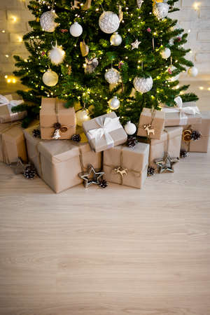 decorated christmas tree with lights and heap of gift boxes - copy space over wooden floor background Фото со стока