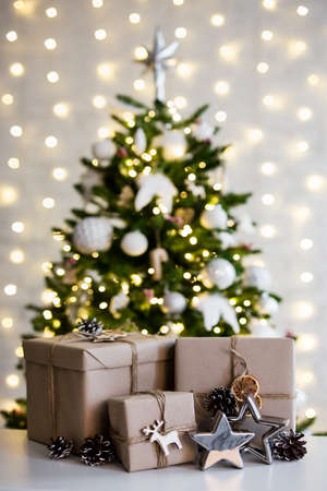 christmas and new year concept - beige gift boxes near decorated christmas tree over white wall with garland lights