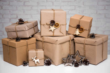close up of beige gift boxes over white brick wall background