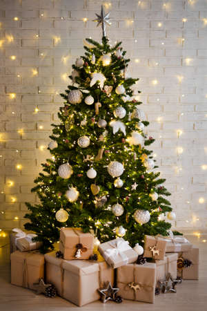 christmas tree and heap of gift boxes over white brick wall with yellow lights