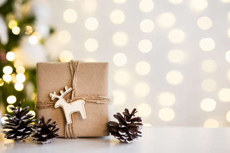 close up of gift box and fir cones near decorated christmas tree over white wall background with lights and copy space Фото со стока - 133314374