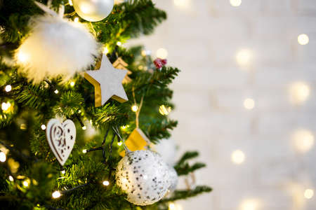 close up of decorated christmas tree with lights and copy space over white wall Фото со стока
