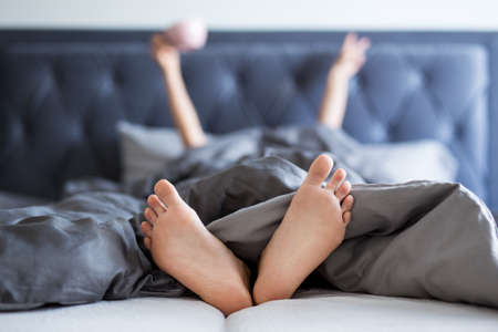 good morning concept - female hands and legs sticking out from the blanket in bedroom Imagens