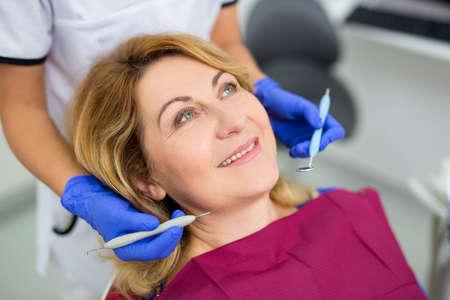 dentist examining mature woman's teeth in dental clinic