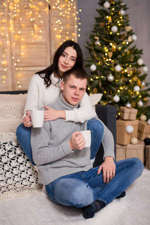 christmas, new year and love concept - cute couple in love drinking tea or coffee near Christmas tree