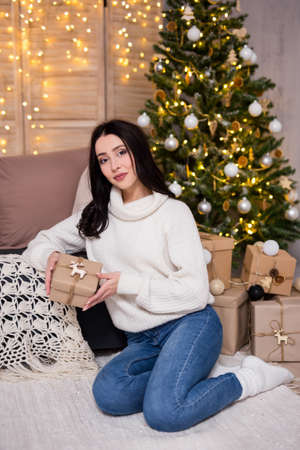 christmas and new year concept - portrait of happy young beautiful woman sitting with Christmas presents near Christmas tree