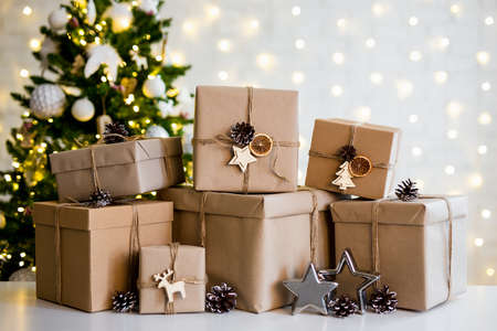 christmas and new year concept - heap of beige gift boxes near decorated christmas tree with lights Фото со стока
