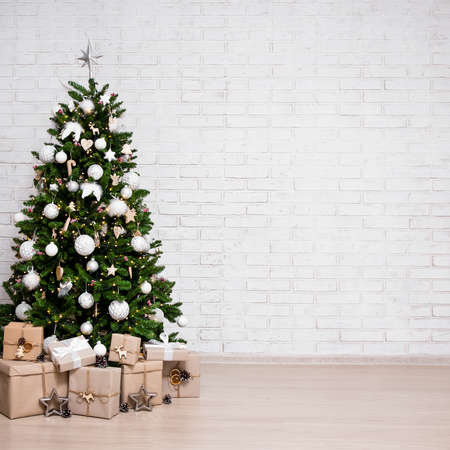 decorated christmas tree, heap of gift boxes over white brick wall background with copy space Фото со стока