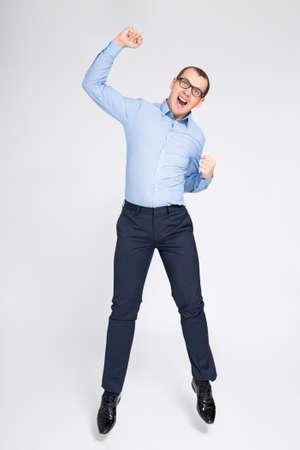 concept de réussite - joyeux jeune homme d'affaires beau célébrant quelque chose et sautant par-dessus fond gris