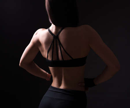back view of sexy girl with muscular body posing over black background