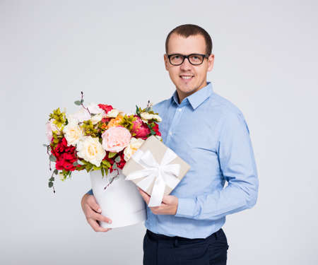 valentines day or mothers day concept - portrait of young handsome man with flowers and gift box over gray background