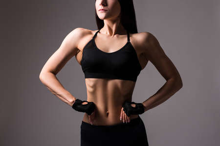 close up of beautiful muscular female body over gray background