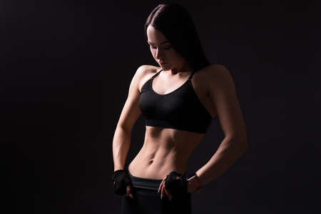 beautiful sexy girl with muscular body posing over black background Фото со стока
