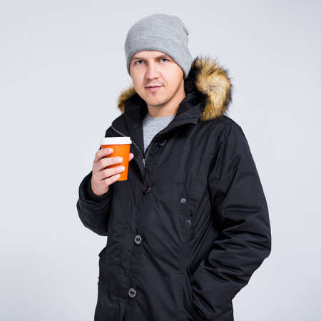 young handsome man in warm winter jacket holding paper cup of coffee over gray background Фото со стока