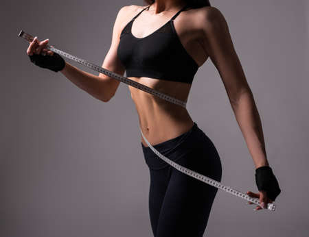 close up of sporty woman with muscular body measuring her waistline with measure tape over gray background