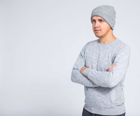 portrait of young handsome man in warm winter clothes posing over gray background with copy space