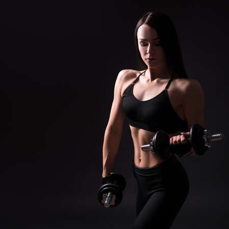 young beautiful sexy girl with muscular body exercising with dumbbells over black background with copy space