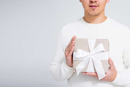 Christmas or Valentines day concept - close up of wrapped gift box in male hands over gray background with copy space