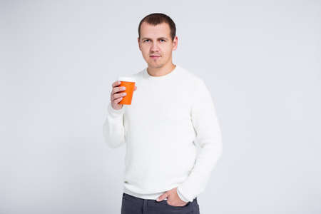 portrait of young man in warm winter sweater holding cup of coffee pr tea over gray background with copy space