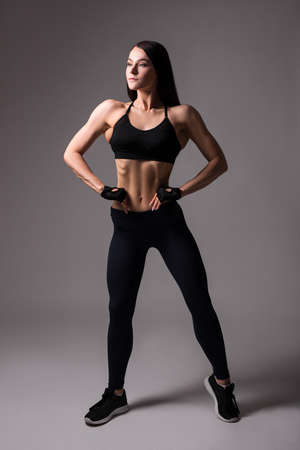 full length portrait of young beautiful sporty woman with muscular body posing over gray background