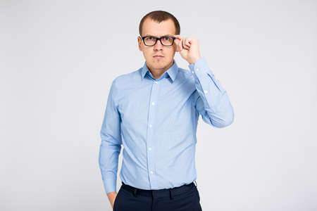 portrait of young businessman in eyeglasses over gray background with copy space