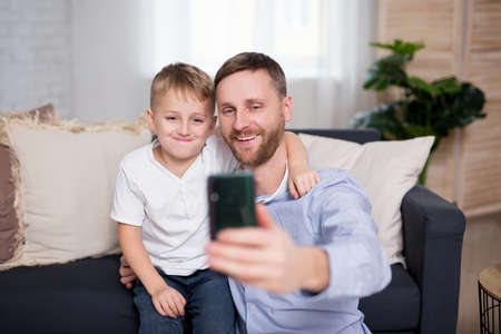 young father and his little son taking selfie photo with smart phone at home
