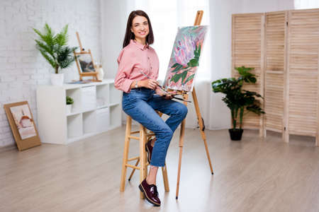 full length portrait of young woman artist with easel, palette and paint brush painting picture at home or studio