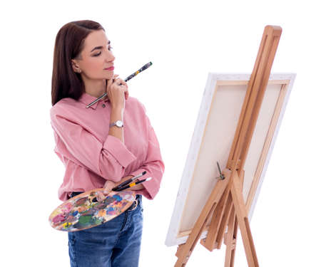 young beautiful woman artist with easel, palette and paint brush painting picture and dreaming about something isolated on white background